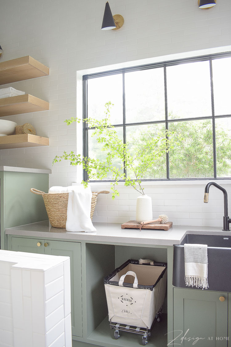 laundry room with gray green cabinets white tiled wall