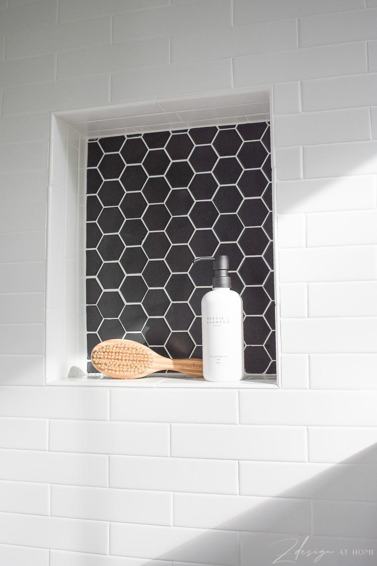 niche in dog shower - black hex tile, white grout
