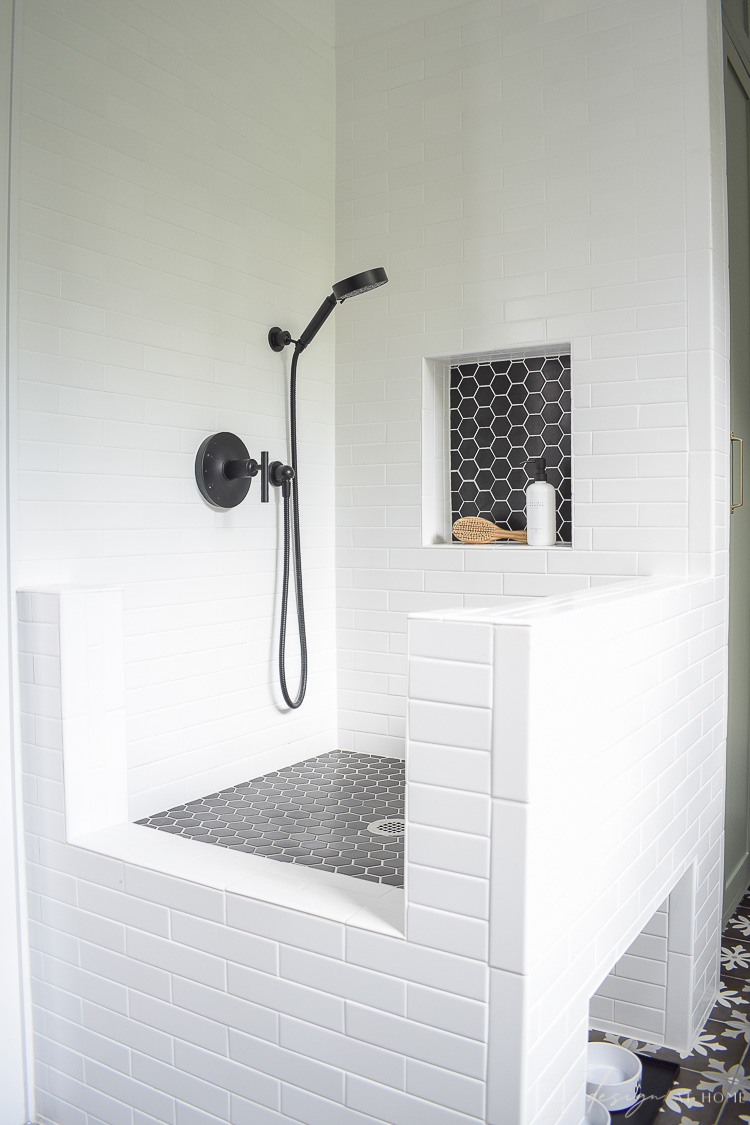 dog wash with white tile and black hex tile with shower niche