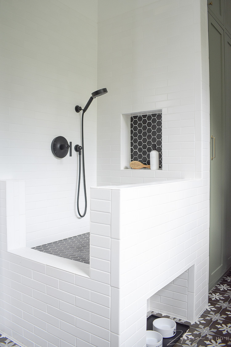 black and white tile dog wash with black hex tile and a shower niche