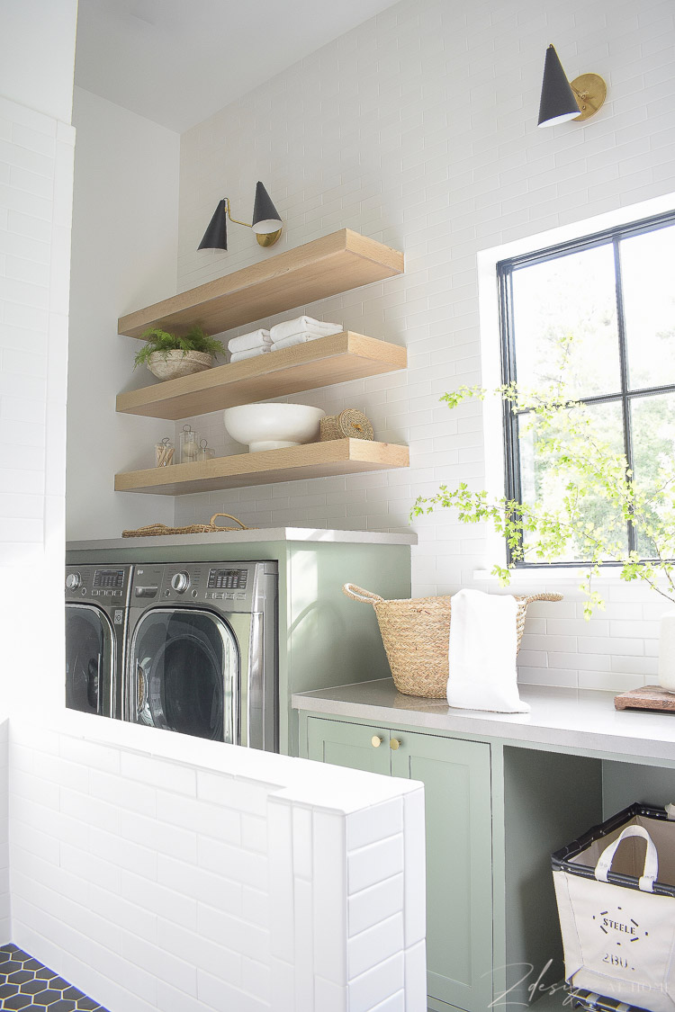 elegant laundry room with white oak shelves and builtin washer dryer
