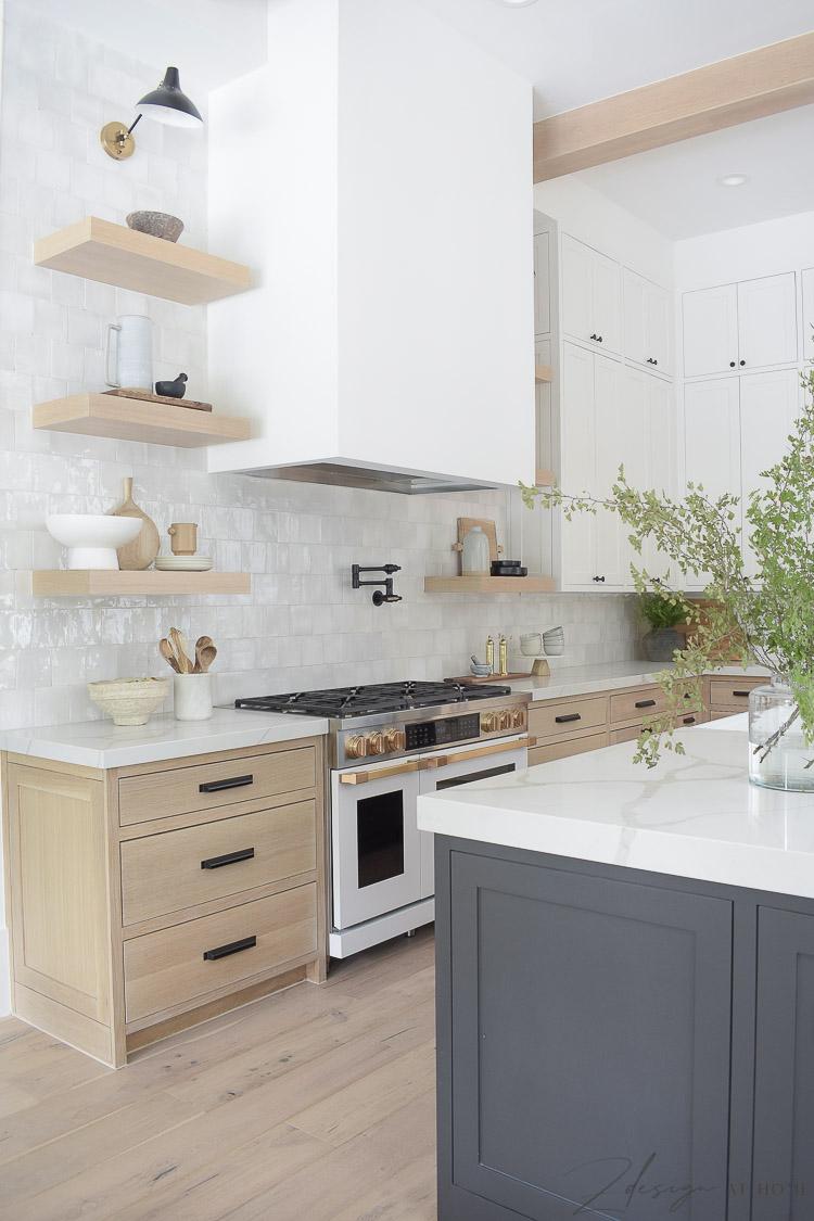 white sheetrock range hood with white oak shelves and cabinets