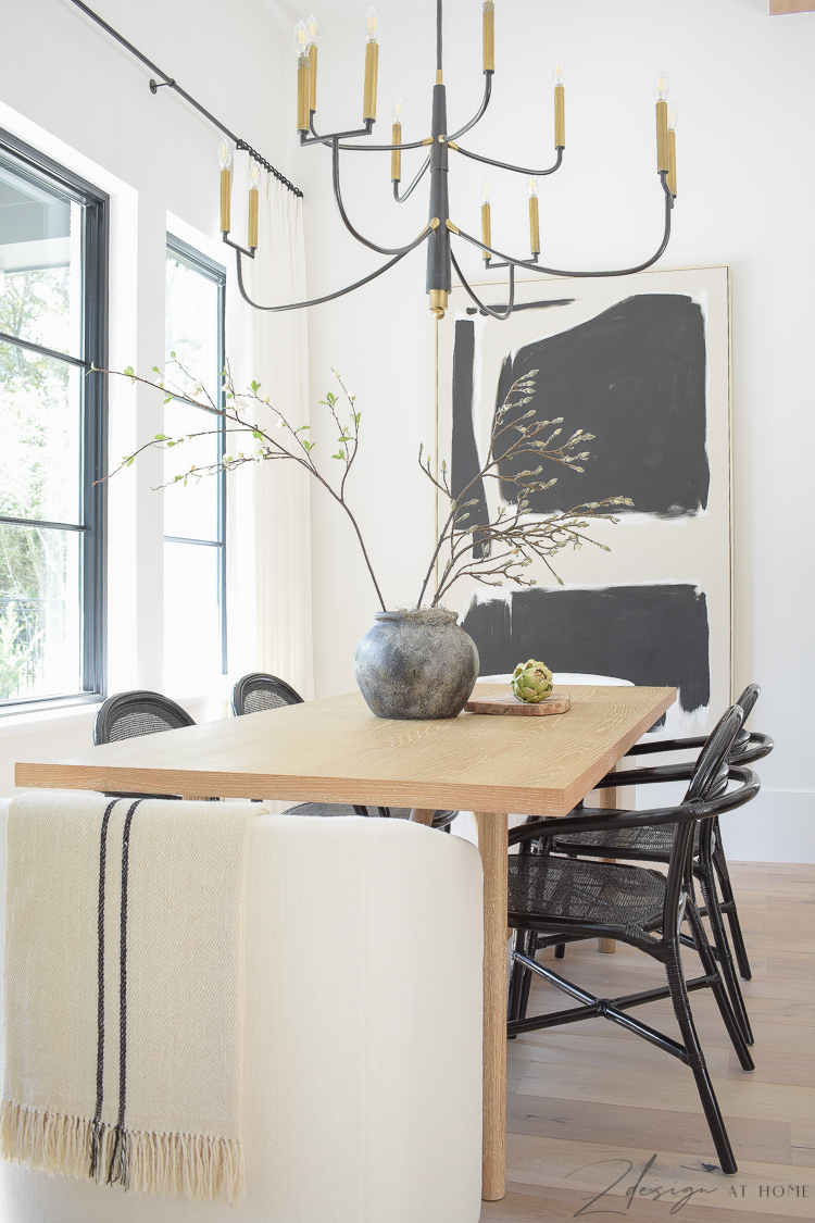 Modern farmhouse black and white themed dining room with black rattan dining chairs and oversized art, brass and black chandelier