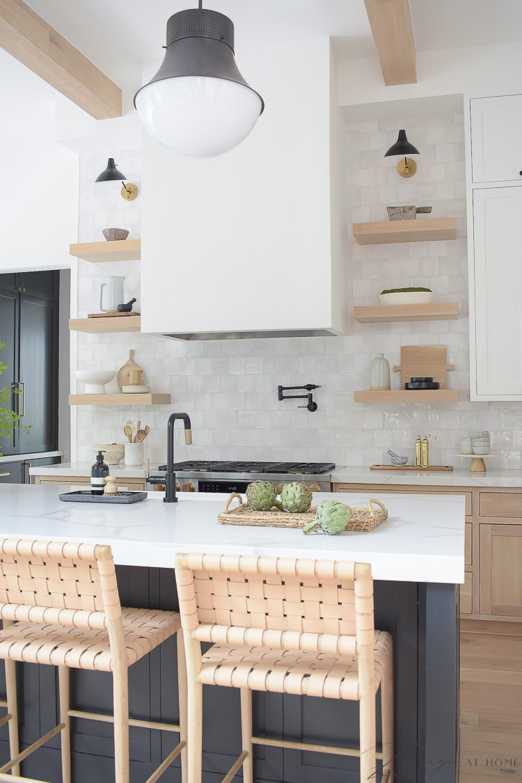 modern farmhouse kitchen with white oak open shelves and zellige tile, black island with quite quartz countertops with veining