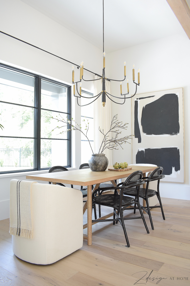 black and white modern farmhouse dining room with oversized art and rattan black chairs