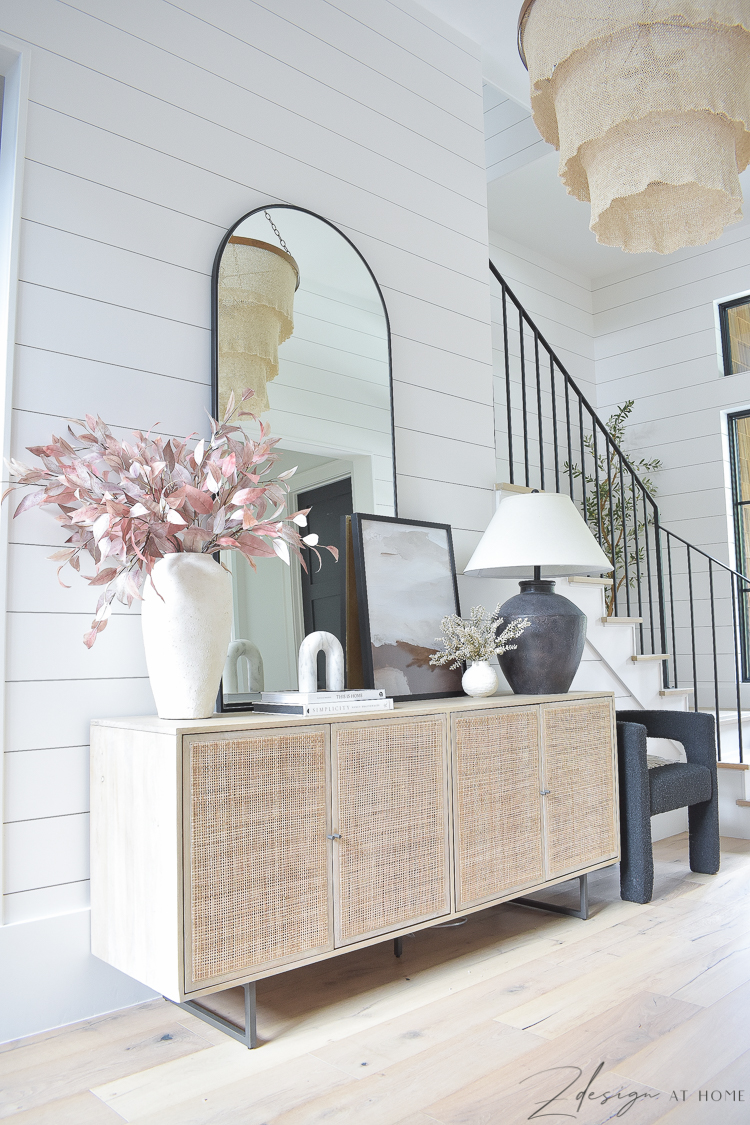 fall entryway with shiplap walls and large arched metal black mirror