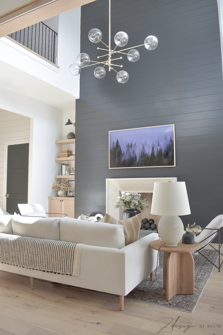 fall decor in a transitional modern living room with black shiplap fireplace